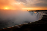 Sunrise over the rising mist of Horseshoe Falls, Niagara Falls, Canada looking back into the United States (USA).