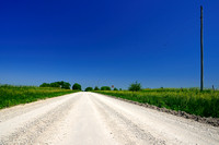 On the Road Again, A Dirt Gravel Road under a Blue SKy in Winterset, Iowa (IA)