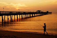 A silhouette of a  Fisherman at Sunrise by a Southern Florida (FL) Pier.